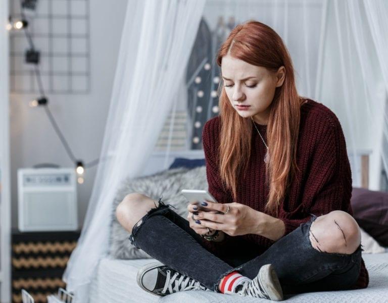 jonge vrouw zit op haar bed en kijkt op haar mobiel