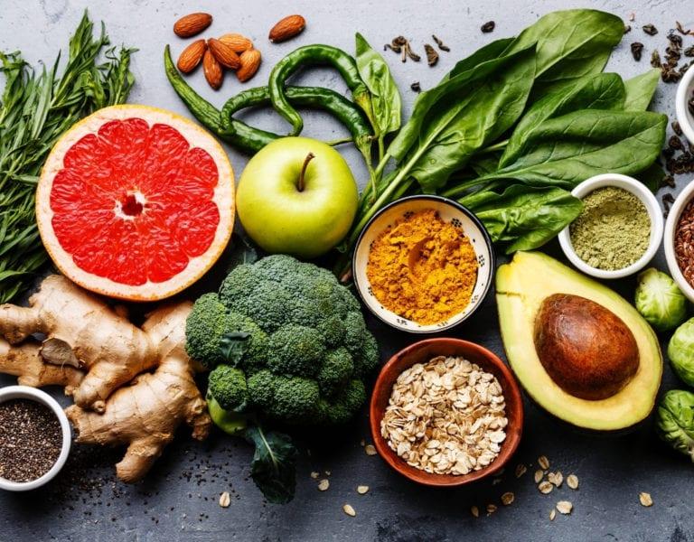 gezonde voeding is belangrijk, gember, brocolli, avocado, lijnzaad, noten, zaden, kruiden, fruit, groenten op een tafel